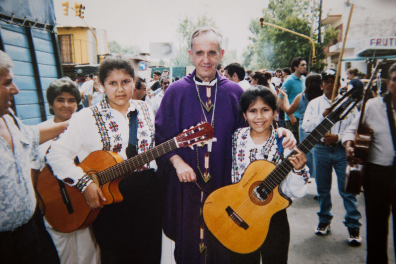 """In this April 2000 photo courtesy of the Espinola family, Buenos Aires' Archbishop Jorge Mario Bergoglio poses for photo with Angela Espinola, 12, left, and her sister Eliza, 9, during an Easter procession organized by the Virgin of Caacupe church in the Villa 21-24 slum in Buenos Aires, Argentina. For more than a billion Catholics worldwide, he's Pope Francis. For Argentina's poorest citizens, who crowd into the many so-called """"misery villages"""" that surround the capital, he's proudly known as one of their own, a true """"slum pope."""" (AP Photo/Courtesy of the Espinola family)"""