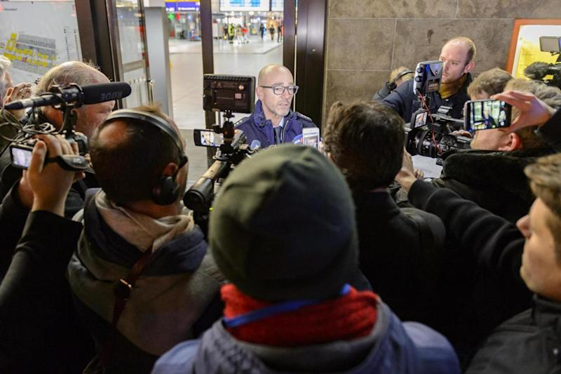 Press and media record officials at the scene of the axe attack. (Getty Images)