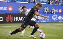 CF Montreal defender Zorhan Bassong controls the ball, moving away from Atlanta United defender Ronald Hernandez during the first half of an MLS soccer match Wednesday, Aug. 4, 2021, in Montreal. (Paul Chiasson/The Canadian Press via AP)