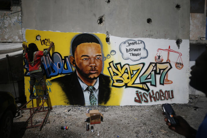 """Artist Bungy Baka puts the finishing touches on a mural of opposition community leader Jose Mano Victorieux, known as """"Badou,"""" who protestors said was executed Saturday night by unknown assailants. in Port-au-Prince, Haiti, Wednesday, Oct. 2, 2019. A small group of men was protesting at the intersection nearby, blocking a main road with barricades until police intervened. (AP Photo/Rebecca Blackwell)"""