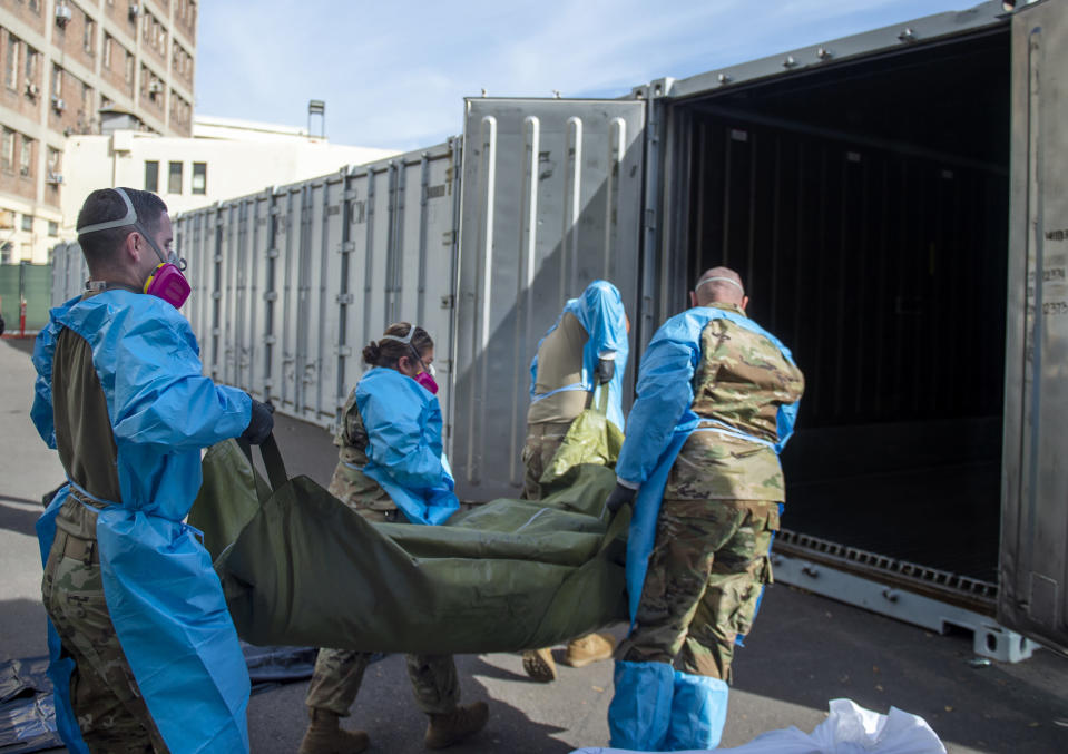 FILE - In this Jan. 12, 2021, file photo provided by the Los Angeles County Department of Medical Examiner-Coroner, National Guard members assist with processing COVID-19 deaths, placing them into temporary storage at the medical examiner-coroner's office in Los Angeles. The coronavirus death toll in California surpassed 50,000 on Wednesday, Feb. 24, 2021, marking about one-tenth of the U.S. total from the pandemic. (Los Angeles County Department of Medical Examiner-Coroner via AP, File)