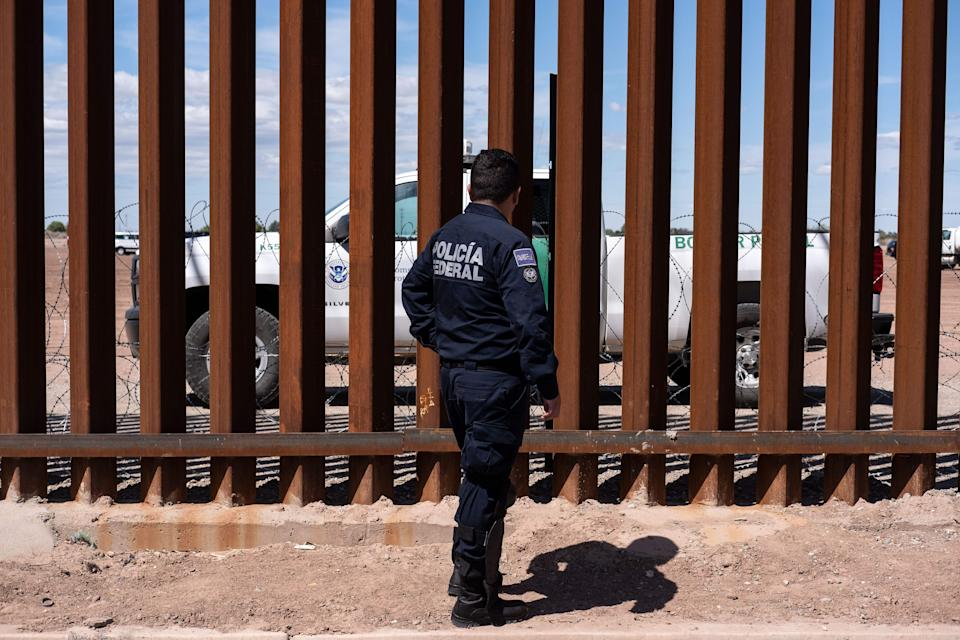 A Border patrol unit (behind the fence) and a Mexico's federal police guard near the US-Mexico border fence as US President Donald Trump visits Calexico, California, as seen from Mexicali, Baja California state, Mexico, on April 5, 2019. - President Donald Trump flew Friday to visit newly built fencing on the Mexican border, even as he retreated from a threat to shut the frontier over what he says is an out-of-control influx of migrants and drugs. (Photo by Guillermo Arias / AFP)        (Photo credit should read GUILLERMO ARIAS/AFP via Getty Images)
