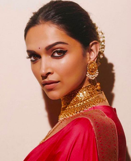"""The Ethnic Siren, Deepika's natural Southern charm makes her look like India in one picture! The beautiful bronze skin, velvety lips and dark smouldering eyes make Deepika an amazing vehicle for portraying Indian beauty! <strong>Get this look</strong> with a cream foundation, <a href=""https://fave.co/2p1IF04"">MyGlamm's Spotlight Illumination Liquid Bronzer</a>, layer on a powder highlighter and bronzer for further definition, a nude lip pencil and matte lipstick in a nude shade. The eyes say it all here, so a black kohl pencil eyeliner on both the upper and lower eyelids and lashings of mascara nail this epitome of the Bharatiya Sundari look."""
