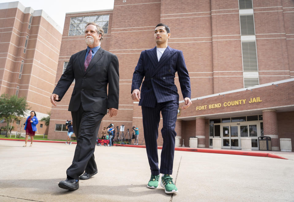 Victor Cuevas, right, walks with his lawyer Michael Elliott after bonding out of jail, Wednesday, May 12, 2021, at the Fort Bend County Jail in Richmond, Texas. Cuevas was arrested Monday after fleeing a Houston Police Officer with a missing tiger in west Houston. Police said Monday that the tiger's whereabouts are not known. (Mark Mulligan/Houston Chronicle via AP)