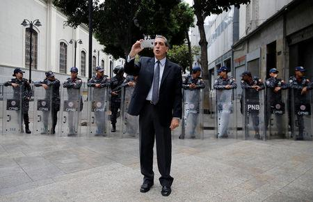 Venezuelan lawmaker Biagio Pilieri broadcasts with his mobile phone near the National Assembly building in Caracas, Venezuela, May 14, 2019. REUTERS/Manaure Quintero