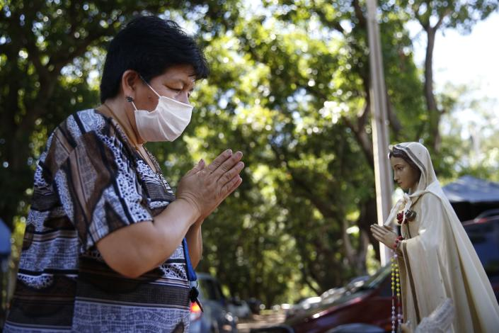 A woman prays before a statue of the Virgin Mary outside the ICU of the Respiratory Hospital INERAM where she has a family member being treated for COVID-19 in Asuncion, Paraguay, Wednesday, March 3, 2021. Without vaccines or basic drugs to combat COVID-19, Paraguay's main public hospitals became unable to receive patients in intensive care units on Wednesday, triggering INERAM Director Felipe Gonzalez to resign in protest. (AP Photo/Jorge Saenz)
