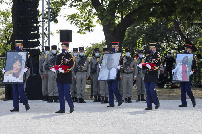 Republican Guards carry the portraits of, from the left, victims Nadine Devillers, Vincent Loques and Brazil's Simone Barreto Silva in Nice, southern France, Saturday Nov. 7, 2020, during a ceremony in homage to the three victims of an attack at Notre-Dame de Nice Basilica on October 29, 2020. Three people were killed in an Islamic extremist attack at Notre Dame Basilica in the city of Nice that pushed the country into high security alert. (Valery Hache; Pool via AP)