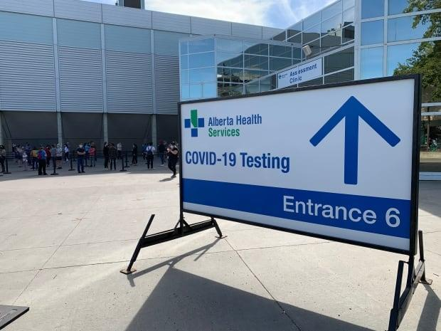 People seeking COVID-19 tests wait at the doors of Edmonton's Expo Centre on Thursday. Alberta reported 1,473 new cases of COVID-19 on Friday.  (Dave Bajer/CBC - image credit)