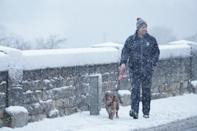 A dog walker makes his way through snow in Hexham, Northumberland. Heavy snow and freezing rain is set to batter the UK this week, with warnings issued over potential power cuts and travel delays. (Photo by Owen Humphreys/PA Images via Getty Images)