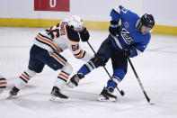 Winnipeg Jets' Nikolaj Ehlers (27) carries by puck past Edmonton Oilers' Kailer Yamamoto (56) during the first period of an NHL hockey game, Sunday, Jan. 24, 2021 in Winnipeg, Manitoba. (Fred Greenslade/The Canadian Press via AP)