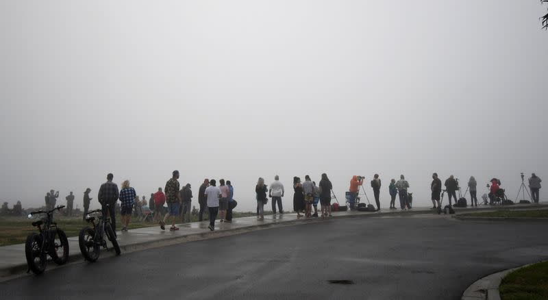 Spectators stand in the fog to try and view the test launch of SpaceX rocket flight SN11