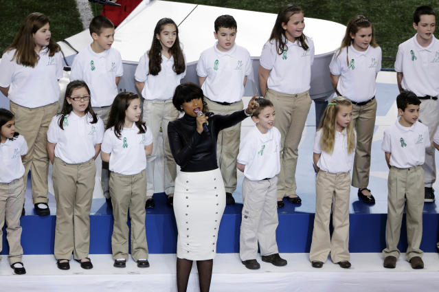 """FILE - In this Feb. 3, 2013 file photo, Jennifer Hudson performs with students from Sandy Hook Elementary School singing """"America the Beautiful"""" before the NFL Super Bowl XLVII football game between the San Francisco 49ers and the Baltimore Ravens in New Orleans. In the weeks since the school shooting, the music world has helped the town come together and heal. (AP Photo/Gerald Herbert, File)"""