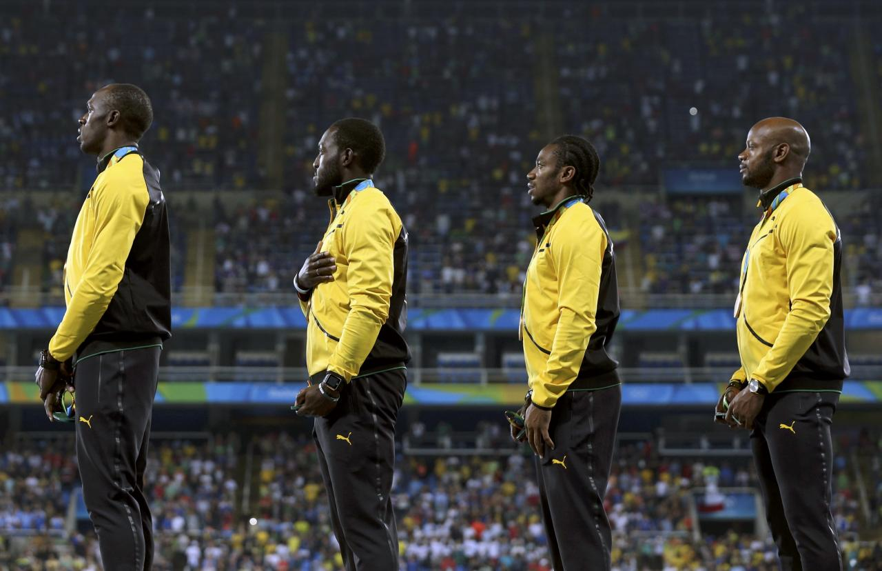 2016 Rio Olympics - Athletics - Victory Ceremony - Men's 4 x 100m Relay Victory Ceremony - Olympic Stadium - Rio de Janeiro, Brazil - 20/08/2016. Gold winners Asafa Powell (JAM), Yohan Blake (JAM), Nickel Ashmeade (JAM) and Usain Bolt (JAM) of Jamaica react on the podium. REUTERS/Dylan Martinez FOR EDITORIAL USE ONLY. NOT FOR SALE FOR MARKETING OR ADVERTISING CAMPAIGNS.