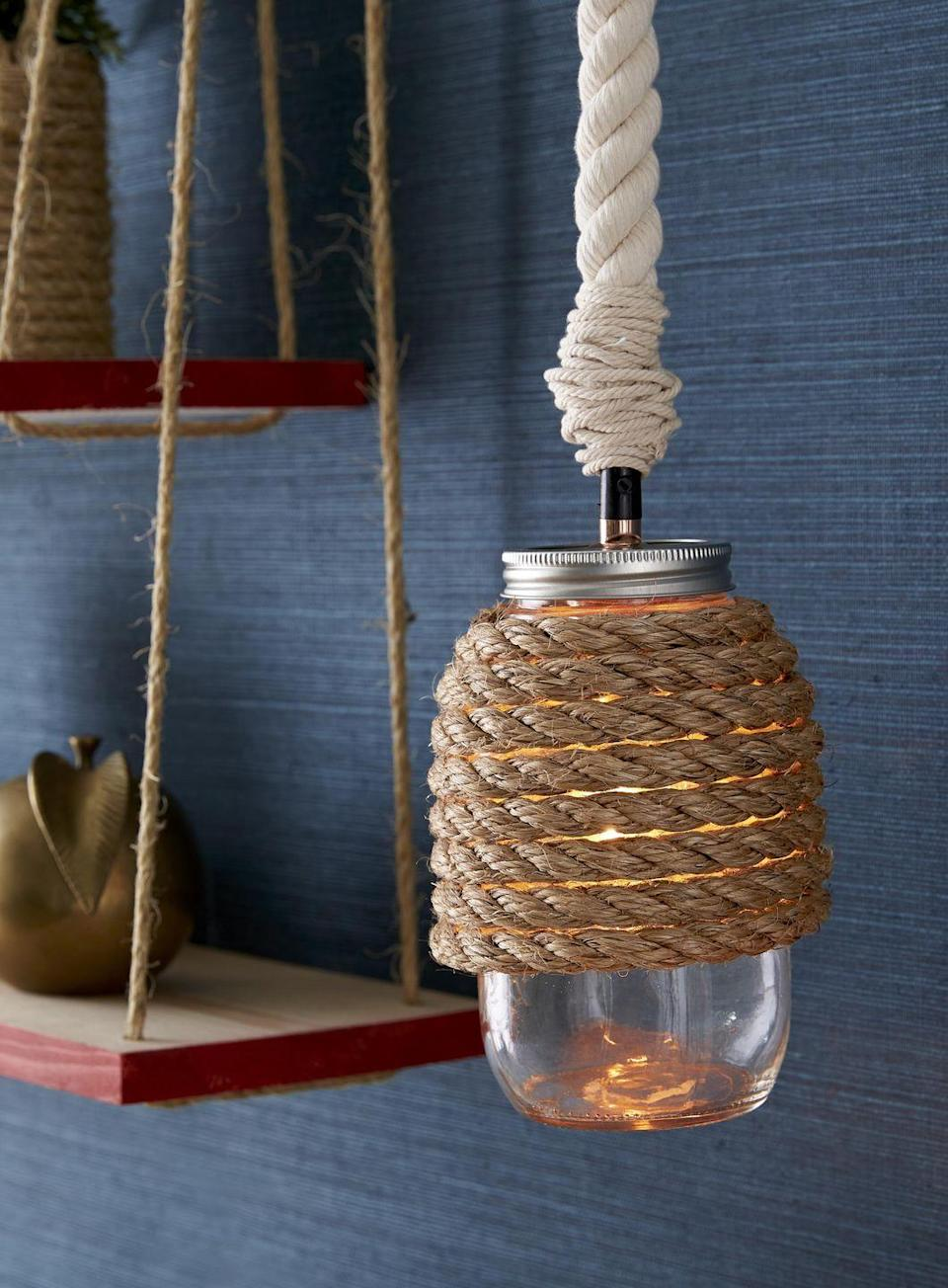 <p>Add a warm subtle glow above your desk or kitchen island with this simple DIY hanging lamp.<br><br><strong>To make:</strong> Hot-glue manila rope to top three-fourths of a regular-mouth mason jar. Wrap the wire of a mason jar pendant light kit with cotton rope, and hold in place with glue. Thread light kit onto jar, and hang.</p>