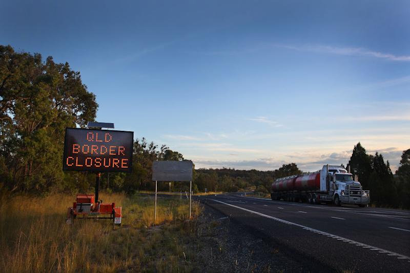 A transport truck makes its way past a border closure sign north of the Queensland border patrol units.