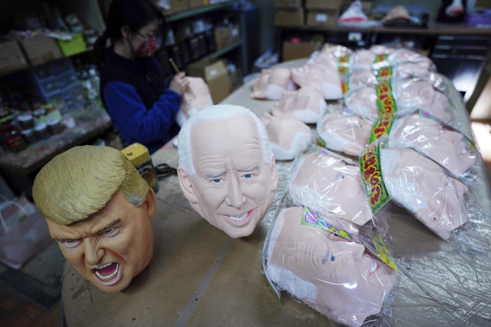 Near the finish products of rubber masks depicting President-elect Joe Biden and President Donald Trump, an employee adds details to the rubber masks at the Ogawa Studios in Saitama, north of Tokyo, Wednesday, Nov. 11, 2020. Ogawa Studios, a Japanese manufacturer started making the masks since the middle of October, ahead of last week's election. (AP Photo/Eugene Hoshiko)