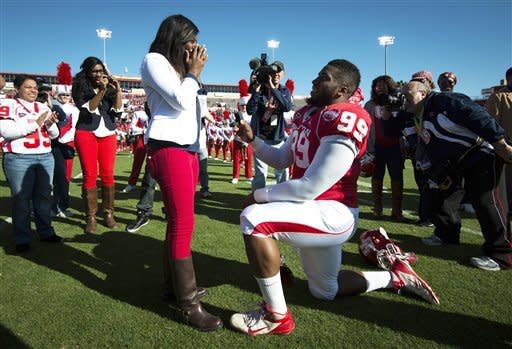 Houston defensive lineman Dominic Miller (99) kneels at midfield as he proposes to his girlfriend Chelsea Johnson before an NCAA college football game against Tulane at Robertson Stadium, Saturday, Nov. 24, 2012, in Houston. Johnson accepted the marriage proposal, which came during senior day festivities. (AP Photo/Houston Chronicle, Smiley N. Pool)