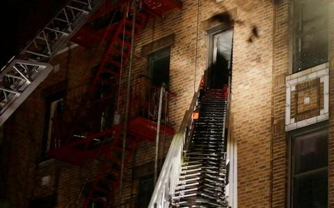 A ladder from a fire truck extends to an apartment window where firefighters respond to a deadly fire - Credit: Frank Franklin/AP