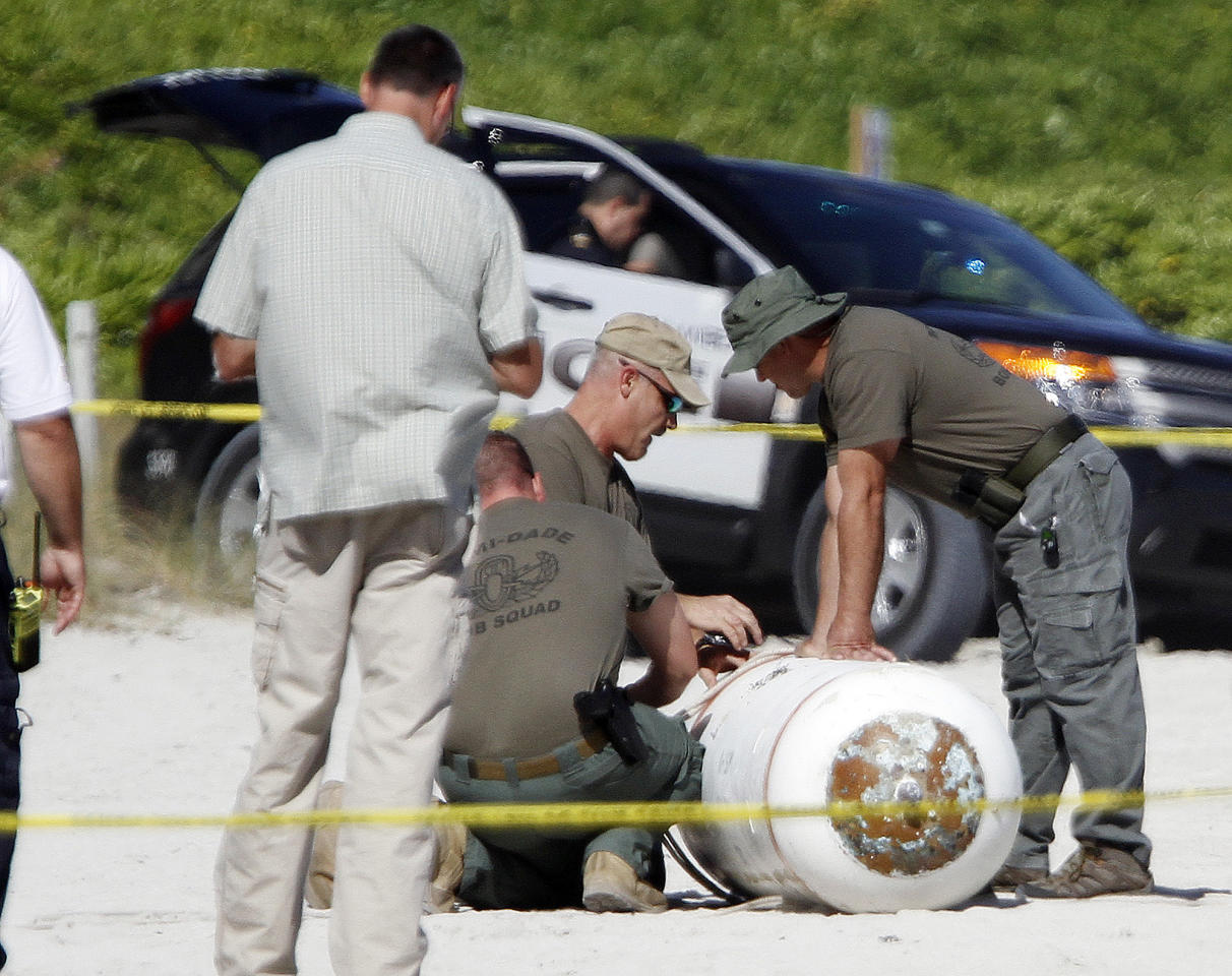 Miami-Dade County bomb squad officers check a live Navy training mine that washed ashore in Miami Beach, Fla., Monday, Dec. 5, 2011. Police cordoned off the area around the beached mine with yellow tape Monday and kept bystanders away as Fire Rescue crews and a bomb squad arrived. Fire Rescue spokesman Jesus Sola says photos of the mine have been taken and sent to the Navy, which will remove the device. (AP Photo/Alan Diaz)