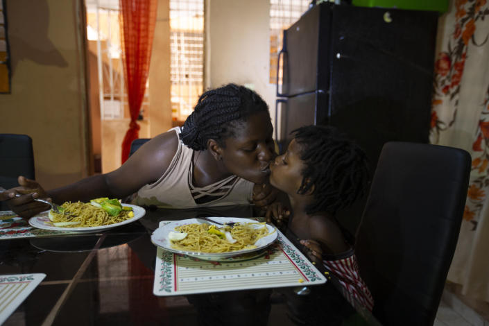 Deported from the United States a day before, Delta de Leon and her 2-year-old daughter Chloe share a kiss in their temporary home, in Port-au-Prince, Haiti, Thursday, Sept. 23, 2021. Breakfast on that first morning in Haiti consisted of spaghetti and bits of avocado. Normally, Chloe has milk and fruit, but de Leon said she was waiting on a money transfer to buy some basic food items. (AP Photo/Joseph Odelyn)