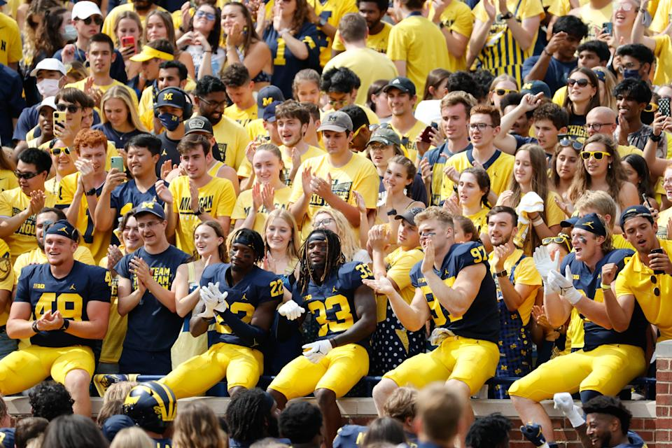 Michigan Wolverines players celebrate in the student section after defeating the Western Michigan Broncos at Michigan Stadium.