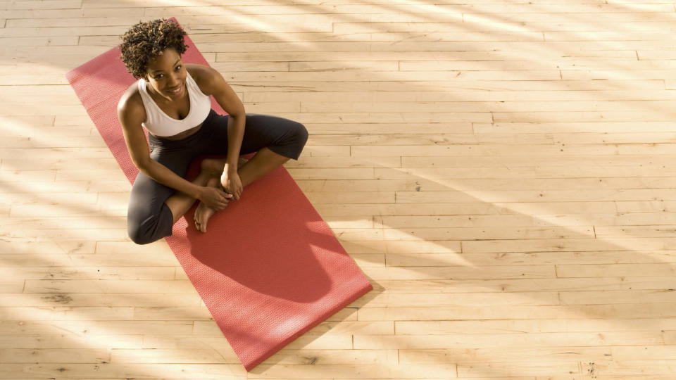 best yoga mats women sitting on red yoga mat from above