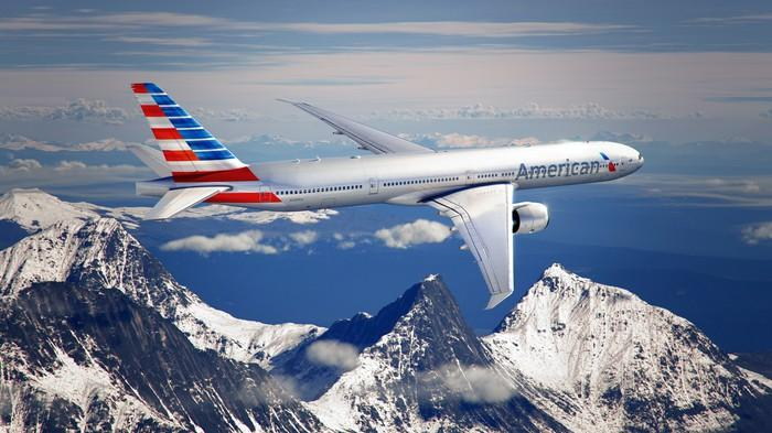 An American Airlines jet in flight, with mountains in the background