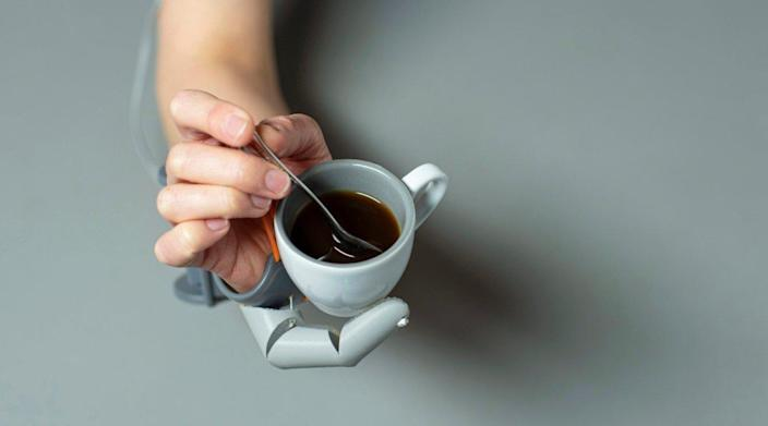 Prosthetic Third Thumb holds a coffee cup while the real thumb uses a spoon to stir in some sugar.