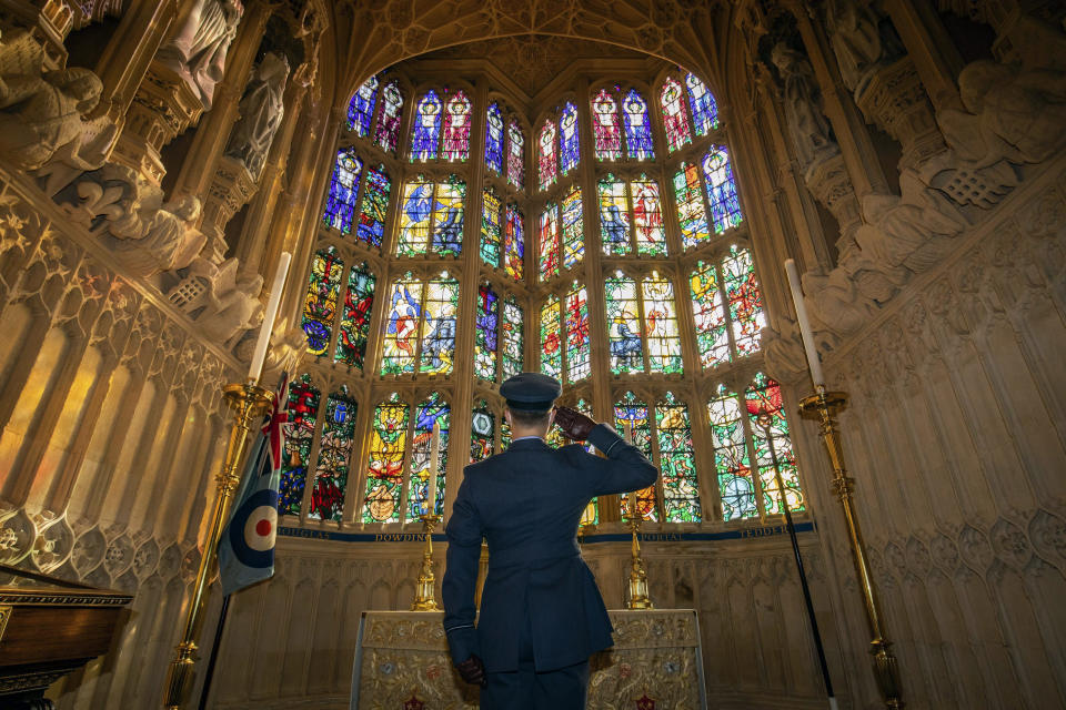 Flying Officer James Buckingham salutes The Battle of Britain memorial window inside Westminster Abbey, the stained glass window by Hugh Easton that contains the badges of the fighter squadrons that took part in the Battle, during a service to mark the 80th anniversary of the Battle of Britain at Westminster Abbey, London, Sunday, Sept. 20, 2020. (Aaron Chown/Pool Photo via AP)