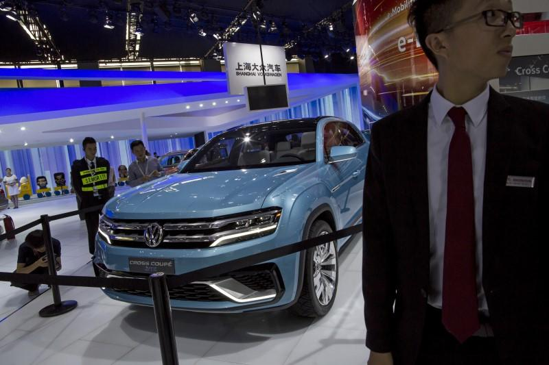 A staff stands next to a Volkswagen Cross Coupe GTE hybrid SUV at the 13th China (Guangzhou) International Automobile Exhibition in Guangzhou, China