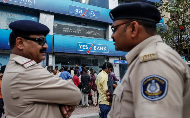 Policemen stand guard as people wait outside a Yes Bank branch to withdraw their money in Ahmedabad