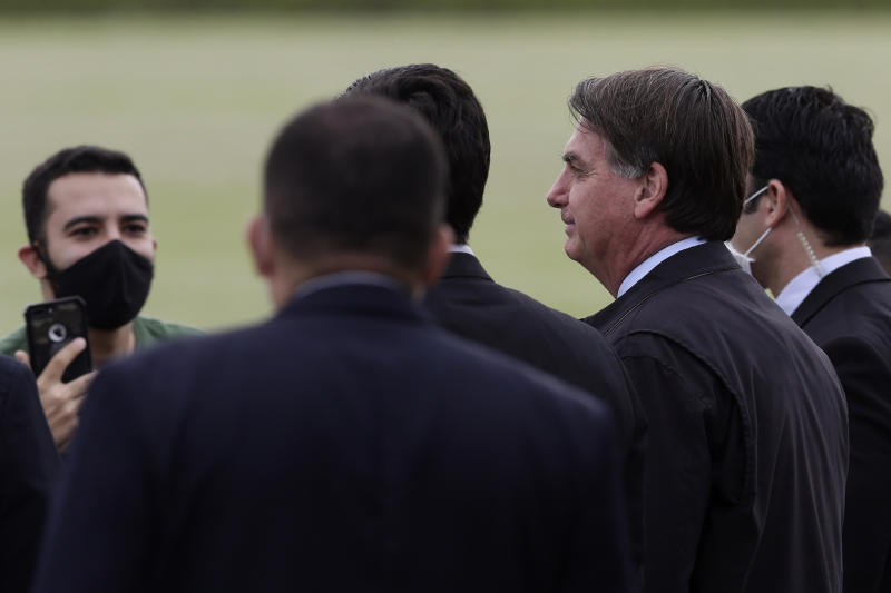 Brazil's President Jair Bolsonaro, second from right, talks with supporters, some wearing face masks amid the new coronavirus pandemic, as he leaves his official residence, Alvorada palace, in Brasilia, Brazil, Monday, May 25, 2020. (AP Photo/Eraldo Peres)
