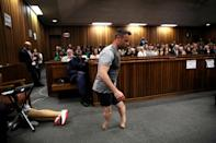 Paralympic gold medalist Oscar Pistorius walks across the courtroom without his prosthetic legs during the third day of the resentencing hearing for the 2013 murder of his girlfriend Reeva Steenkamp, at Pretoria High Court, South Africa June 15, 2016. REUTERS/Siphiwe Sibeko/Files TPX IMAGES OF THE DAY