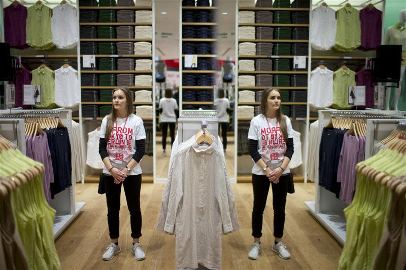 A shop assistant is reflected in the mirror as she stands in the Uniqlo Global flagship store during a preopening in Berlin