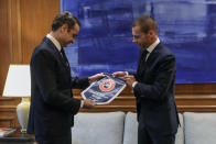 Greece's Prime Minister Kyriakos Mitsotakis, left, receives a gift from UEFA President Aleskander Ceferin, during their meeting in Athens, Tuesday, Feb. 25, 2020. Mitsotakis requested UEFA's help to clean up Greek soccer last month and has said he was willing to request expulsion of Greece's teams from European competition and even suspend the league unless major clubs sign up to a reform plan aimed stamping out match-related violence and widespread allegations of corruption in the sport. (AP Photo/Petros Giannakouris)