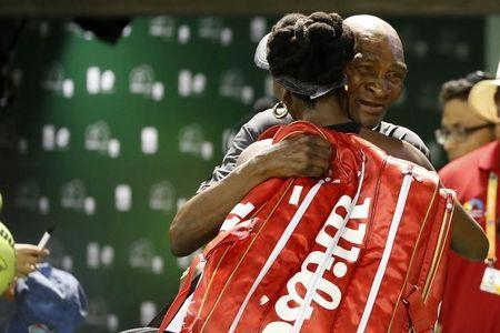 Mar 29, 2017; Miami, FL, USA; Venus Williams of the United States (L) hugs her father Richard Williams (R) while leaving the court after her match against Angelique Kerber of Germany (not pictured) on day nine of the 2017 Miami Open at Crandon Park Tennis Center. Williams won 7-5, 6-3. Mandatory Credit: Geoff Burke-USA TODAY Sports