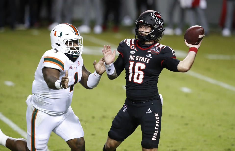 North Carolina State quarterback Bailey Hockman (16) prepares to pass while pressured by Miami defensive lineman Nesta Jade Silvera (1) during the first half of an NCAA college football game Friday, Nov. 6, 2020, in Raleigh, N.C. (Ethan Hyman/The News & Observer via AP, Pool)
