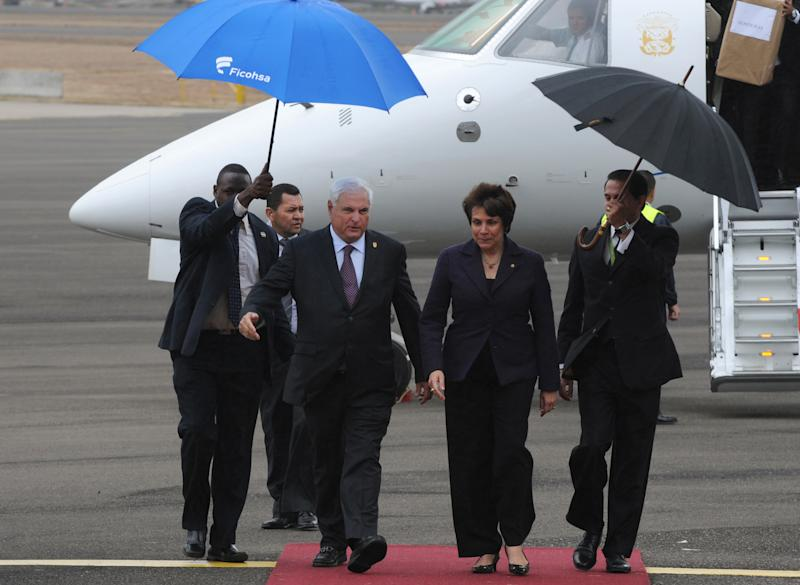 Panama's President Ricardo Martinelli, left, walks with Mireya Aguero, Honduran deputy foreign affairs minister, upon his arrival at the air force base in Tegucigalpa, Honduras, Tuesday March, 6, 2012. Martinelli along with other Central Americans leaders arrived in Honduras to meet with Vice President Joe Biden who is in the country for a one-day official visit. The vice president's two-day trip to Mexico and Honduras comes amid calls by many of the region's leaders to discuss decriminalizing drugs as a way to ease a vicious war on cartels that has left Latin America bloodied. (AP Photo/Fernando Antonio)