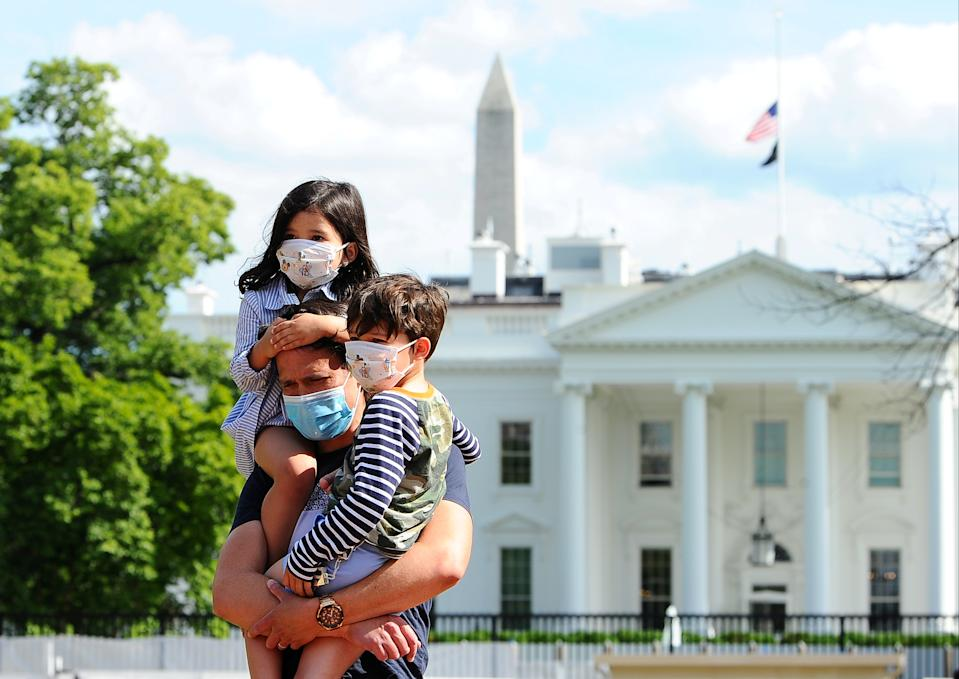 Jason Aguirre carries his children, Elle, 4, and Shai, 6, after viewing the White House, where flags fly at half-staff to commemorate the victims of the coronavirus disease (COVID-19), in Washington, U.S., May 23, 2020. REUTERS/Mary F. Calvert     TPX IMAGES OF THE DAY
