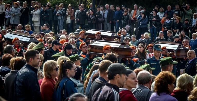 Rescuers carried coffins of victims of the school shooting to the cemetery in the Crimean city of Kerch