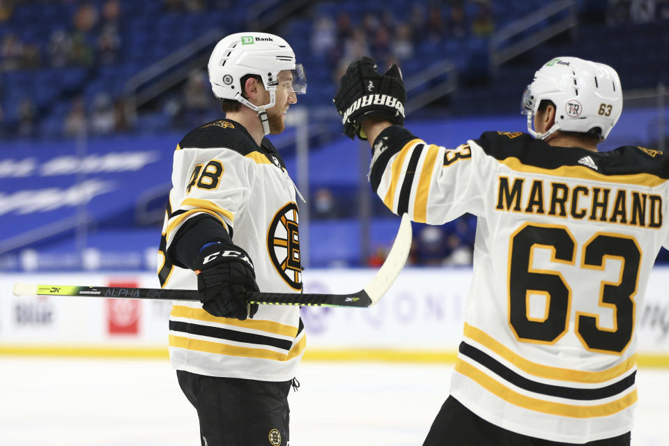 Boston Bruins forward Matt Grzelcyk (48) celebrates his goal with forward Brad Marchand (63) during the second period of the team's NHL hockey game against the Buffalo Sabres, Thursday, April 22, 2021, in Buffalo, N.Y. (AP Photo/Jeffrey T. Barnes)