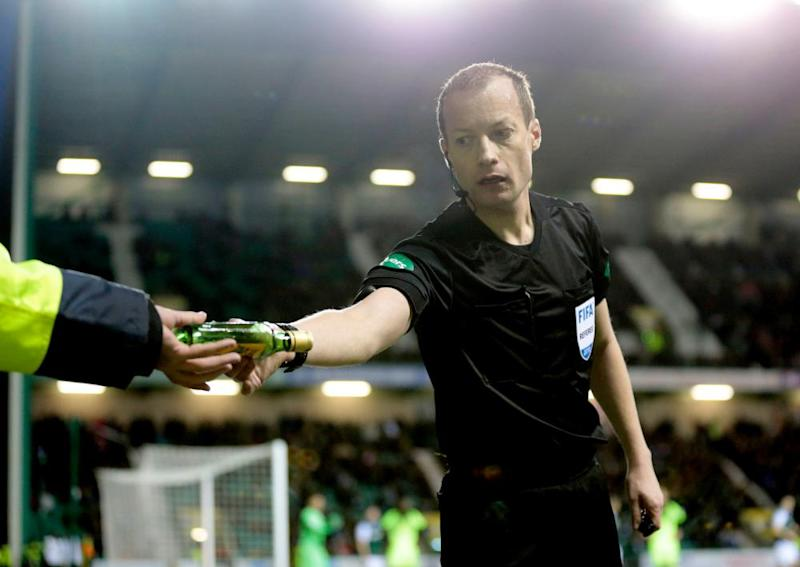 Referee Willie Collum removes a bottle from the pitch during Hibernian v Celtic in the Scottish Cup at Easter Road.