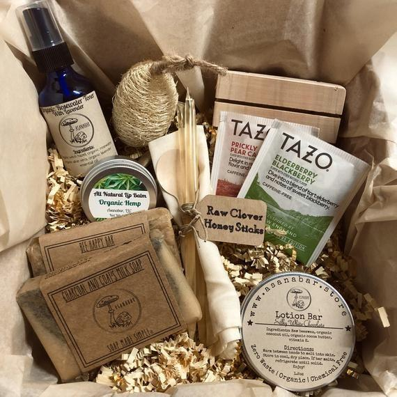 """<p><strong>Asanabar Soaps</strong></p><p>etsy.com</p><p><strong>$42.00</strong></p><p><a href=""""https://go.redirectingat.com?id=74968X1596630&url=https%3A%2F%2Fwww.etsy.com%2Flisting%2F762528743%2Forganic-gift-box-handmade-natural&sref=https%3A%2F%2Fwww.goodhousekeeping.com%2Fholidays%2Fgift-ideas%2Fg34054234%2Fbest-gift-baskets-for-women%2F"""" rel=""""nofollow noopener"""" target=""""_blank"""" data-ylk=""""slk:Shop Now"""" class=""""link rapid-noclick-resp"""">Shop Now</a></p><p>This organic-themed basket features handmade soaps, natural lip balm, organic teabags, raw honey sticks, and more.</p>"""
