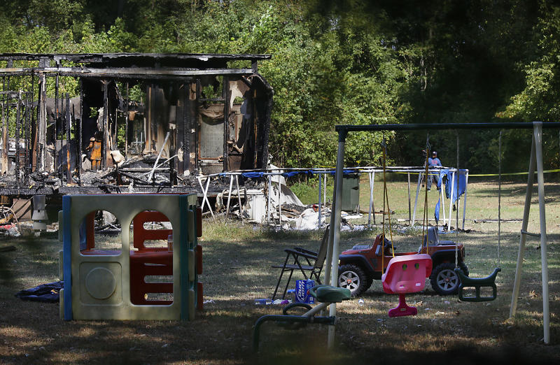 Emergency personnel sift through the scene of an overnight fire that killed three adults and two children in Atoka, Tenn., Tuesday, Sept. 28, 2010.  Two children escaped the fire by breaking out of a bedroom window. (AP Photo/Lance Murphey)