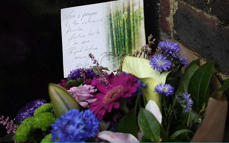 A bunch of flowers are left as a tribute near the burning - Credit: Carl Court/Getty