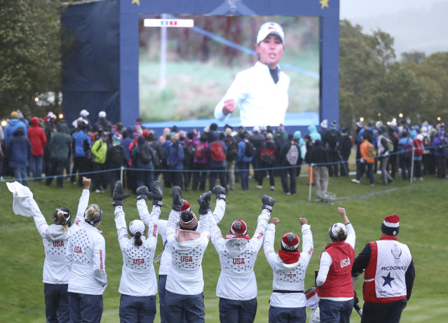 Members of the US team celebrate on the 18th green as they watch Danielle Kang win 2&1 against Europe during the afternoon Fourballs in the Solheim cup at Gleneagles, Auchterarder, Scotland, Saturday, Sept. 14, 2019. (AP Photo/Peter Morrison)