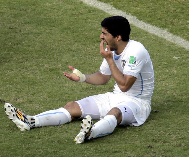 Uruguay's Luis Suarez holds his teeth after running into Italy's Giorgio Chiellini's shoulder during the group D World Cup soccer match between Italy and Uruguay at the Arena das Dunas in Natal, Brazil, Tuesday, June 24, 2014. (AP Photo/Hassan Ammar)