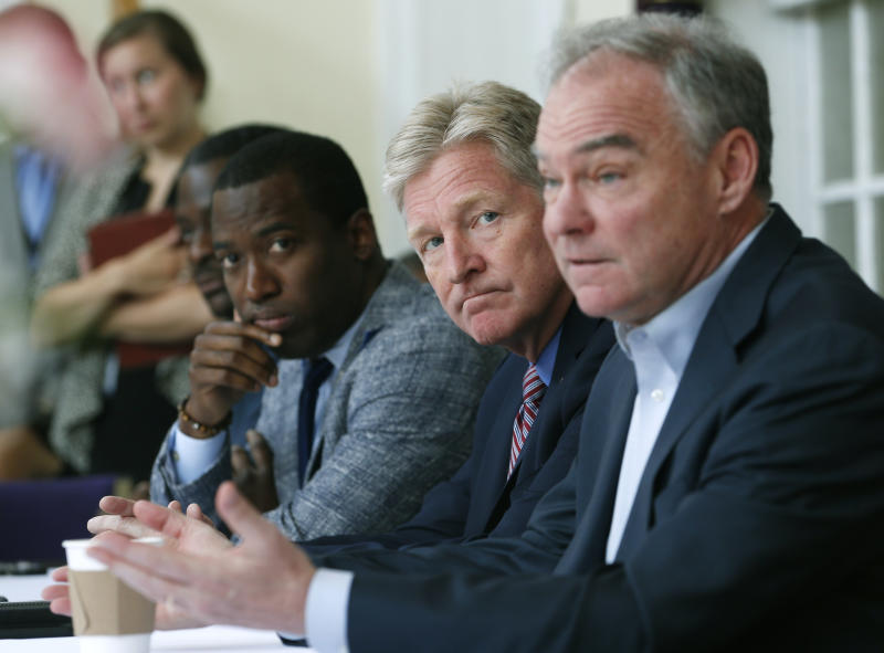 U.S. Sen. Tim Kaine, D-Va., right, gestures during a gun violence prevention roundtable discussion along with Richmond Mayor Levar Stoney, left, and Virginia Secretary of Public Safety, Brian Moran, center, in Richmond, Va., Monday, June 17, 2019. (AP Photo/Steve Helber)