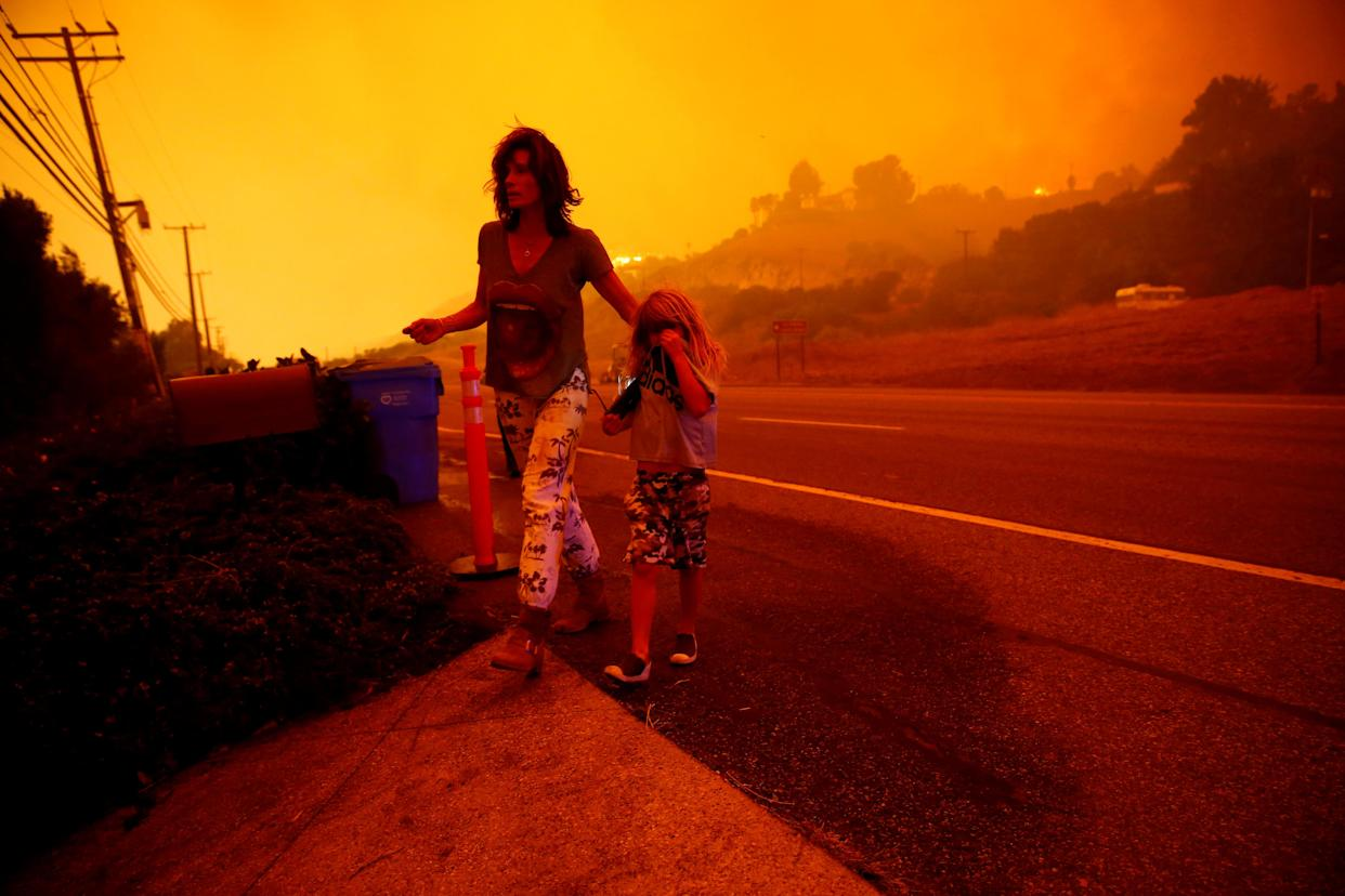 Gabi and Jonah Frank walk on Pacific Coast Highway as the Woolsey Fire threatens their home in Malibu, Calif., Nov. 9, 2018. (Photo: Eric Thayer/Reuters)