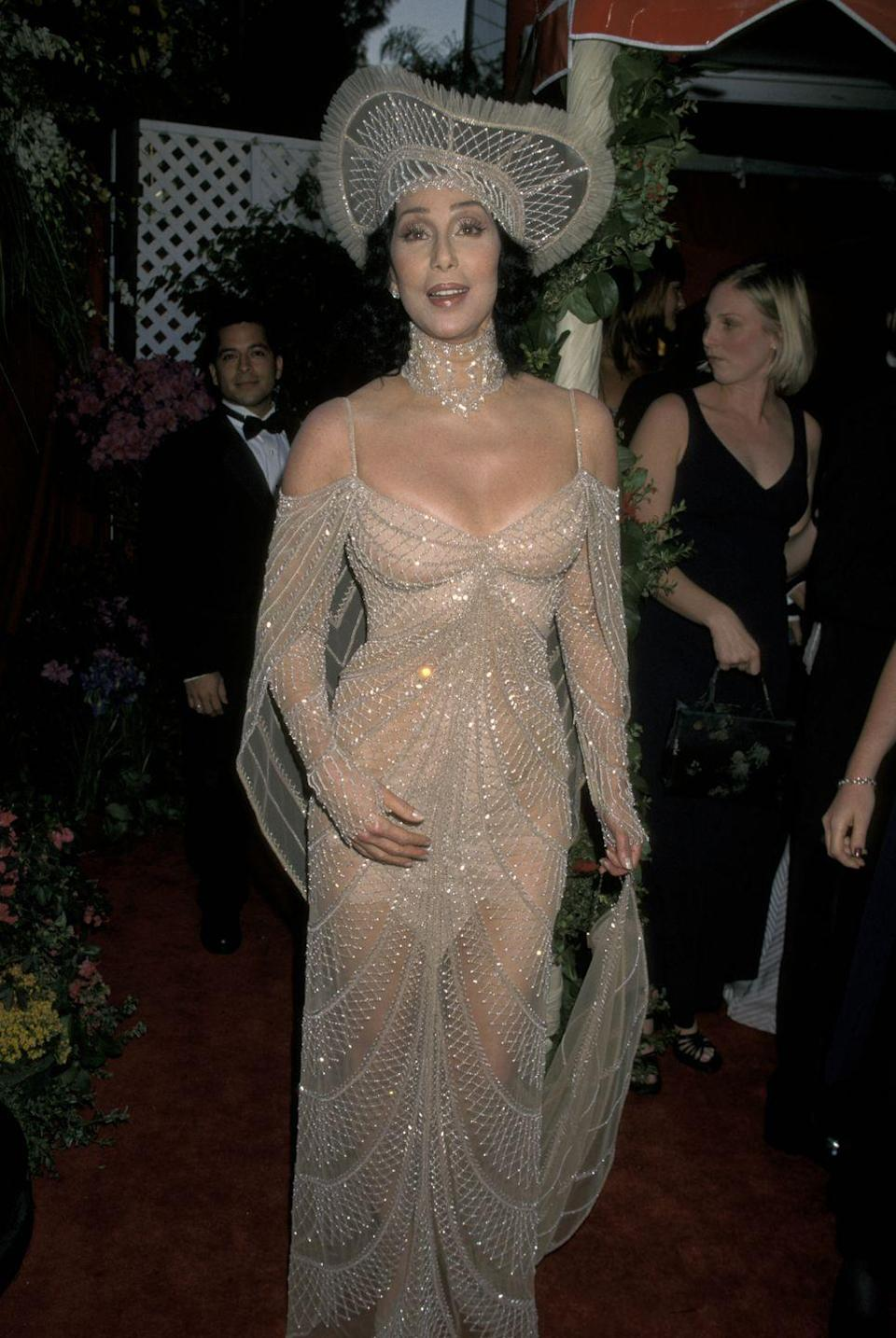 <p>Cher rolled up to the Oscars in this see-through cold-shoulder embellished gown that also had a matching choker and headpiece. It even had a train for an extra ~dramatic~ effect. </p>